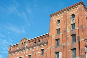 Perspective of old orange bricklayers building in the sunny day photo