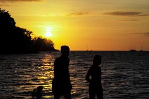 Silhouette portrait of sweet couple walking on the beach at sunset photo