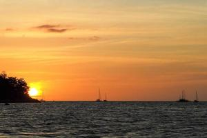 Silhouette of island and yachts on the horizon line with light of sunset photo