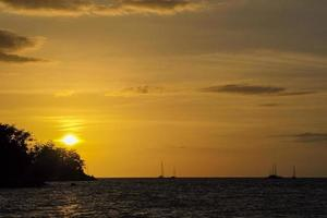 Silhouette of island and yacht boats on the horizontal line with light of sunset photo