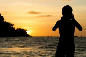 Silhouette portrait of young boy taking a seascape scene on the beach with light of sunset photo