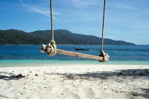 Selective focus on old wooden swing hanging from the tree with defocused sea background photo