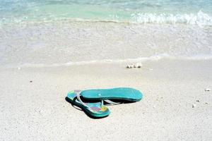 Closeup pair of old sandals on the white sand beach photo