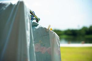 Closeup of many pieces of rags hanging with clothespin for drying in the sunlight photo