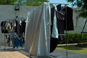 Many pieces of clothes hanging on the stainless rack for drying with the sunlight. photo