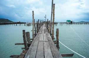 Native fisherman house and traditional fishing farm at the coast of sea with old wooden walkway photo