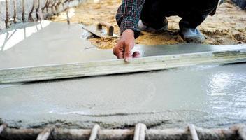 Trabajador con llana de madera para nivelar el piso de concreto foto