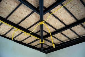 The electrical yellow pipes under installation on the steel roof structure photo