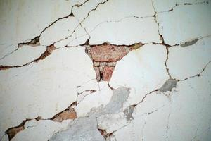 Abstract background and texture of broken cement wall with brick layers inside