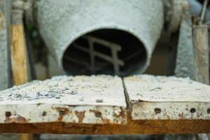 Selective focus on group of crashed stones on the steel plate with blurred concrete mixer
