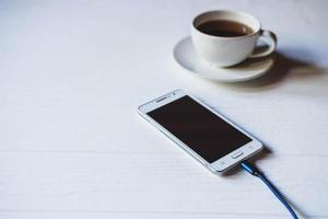 Phone on charger with coffee photo