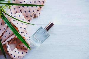 Flat lay of perfume with a plant and ribbon