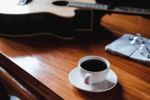 Coffee and guitar on a desk