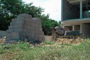 paisaje del sitio de construcción con la pila de materiales, equipos y maquinaria con desenfocado de hierba de flores en el fondo. foto