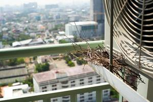 Closeup bird nest on the steel cage of air conditioner at the terrace of high condominium with blurred cityscape background photo
