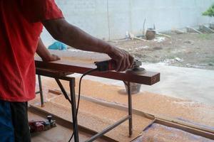 Primer plano de la mano del carpintero sostiene la herramienta eléctrica fregando la superficie de la madera foto