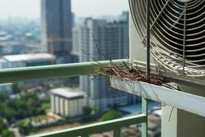 Closeup bird nest on the steel cage of air conditioner at the terrace of high condominium with blurred cityscape background in sunshine morning photo