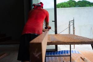 Back portrait of carpenter holds electrical tool scrubbing the surface of wood for woodwork at the construction site
