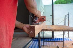 Closeup hand of carpenter holds electrical tool scrubbing the surface of wood