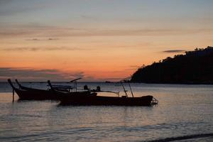 Silhouette group of traditional long tail boats floating in the sea with twilight of sunset and island in background