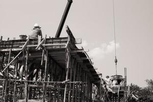Monochrome of workers carrying the cement container to pour at site