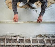 Worker using wooden trowel for leveling the concrete floor