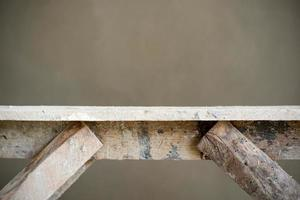 Abstract texture and background of closeup wooden table with wet plastered cement wall in background photo