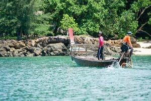 Ko Lanta, Krabi, Thailand 2019 - Fishermen drive the traditional long-tail boat and find fish by tools in sunny day with defocused island in background photo