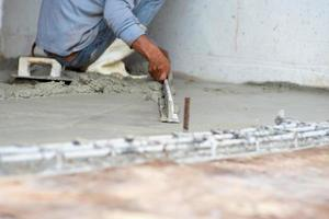Selective focus on the hands of workers using the wooden trowel flatting the surface of the cement floor