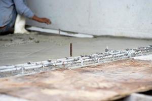 El enfoque selectivo en el acero de refuerzo en el piso de cemento en el sitio de construcción con trabajador borrosa en segundo plano. foto