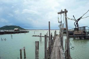 Perspective wooden walkway into the sea with cloudy sky background photo