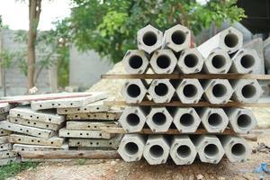 Primer plano montón de pilas hexagonales en el sitio de construcción con árbol borrosa en segundo plano. foto