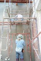 Grupo de trabajadores de pie sobre los andamios de acero y construye un muro de cemento enlucido en la casa en construcción foto