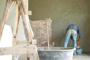 Selective focus on wooden holder in the mixed cement bucket with blurred worker and plastered cement on bricklayer wall in background