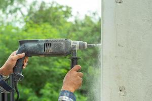 Closeup hands of worker holding an electrical drilling machine and drills into the cement wall photo