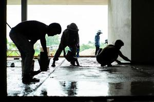 Silhouette group of workers in the house under construction photo