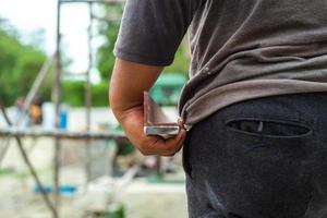 Primer plano de la mano del trabajador sostiene la placa de acero de refuerzo con andamios borrosa en segundo plano en el sitio de construcción foto
