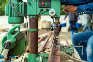 Primer enfoque selectivo en las manos del trabajador controla la máquina perforadora eléctrica para perforar el orificio en la barra de acero en ángulo en el sitio de construcción foto
