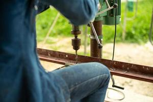 Primer enfoque selectivo en la espalda retrato de trabajador controla la máquina perforadora eléctrica para perforar el orificio en la barra de acero en ángulo en el sitio de construcción foto