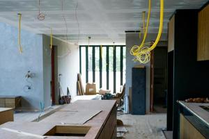 Selective focus on electrical wire hanging from ceiling with perpsective of house under construction photo