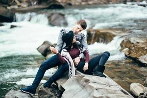 Guy and girl in warm sweaters walking along a mountain river, love story photo