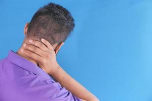 Man holding neck in pain from behind photo