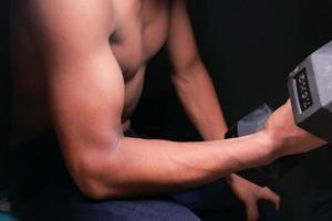 hombre ejercitando bíceps con pesas libres foto