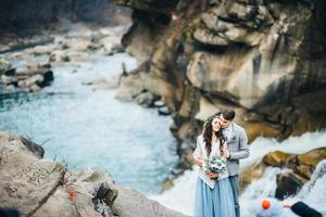 Young couple in love on a mountain river photo