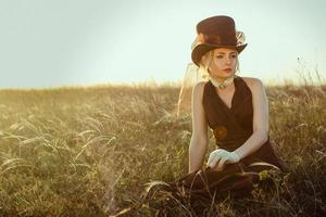 Young blonde girl in a brown vintage dress and top hat in the grass