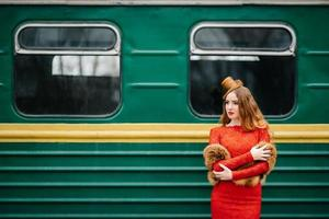 Young girl with red hair in a bright red dress near an old passenger car