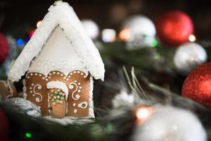 Gingerbread house in the white glaze on the background of the Christmas decorations