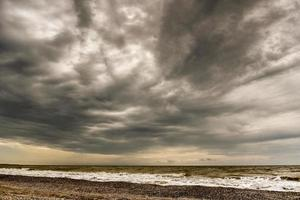 Sullen red sea covered by dark clouds photo