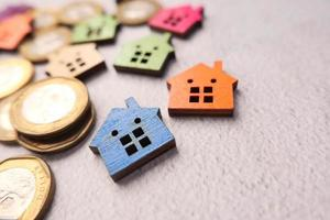 Coins with small model homes on a surface