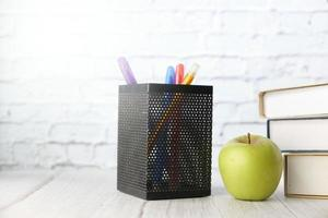 manzana y bolígrafos sobre un escritorio foto